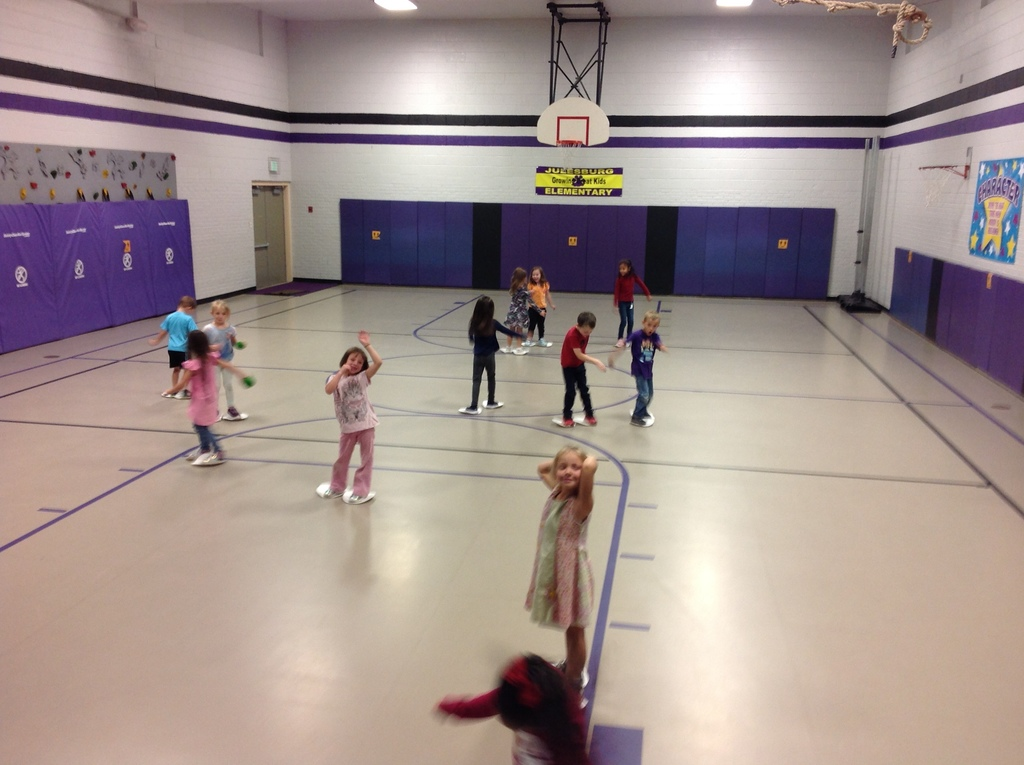 Kindergarten having fun moving their feet with paper plates.