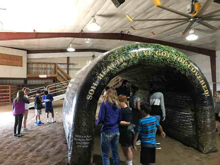 Students learning about soil health with the USDA Natural Resource Conservation's Soil Tunnel.