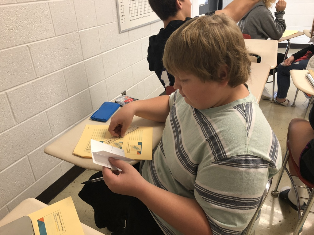 The freshmen students in Geometry are modelling the intersections of two planes using note cards.