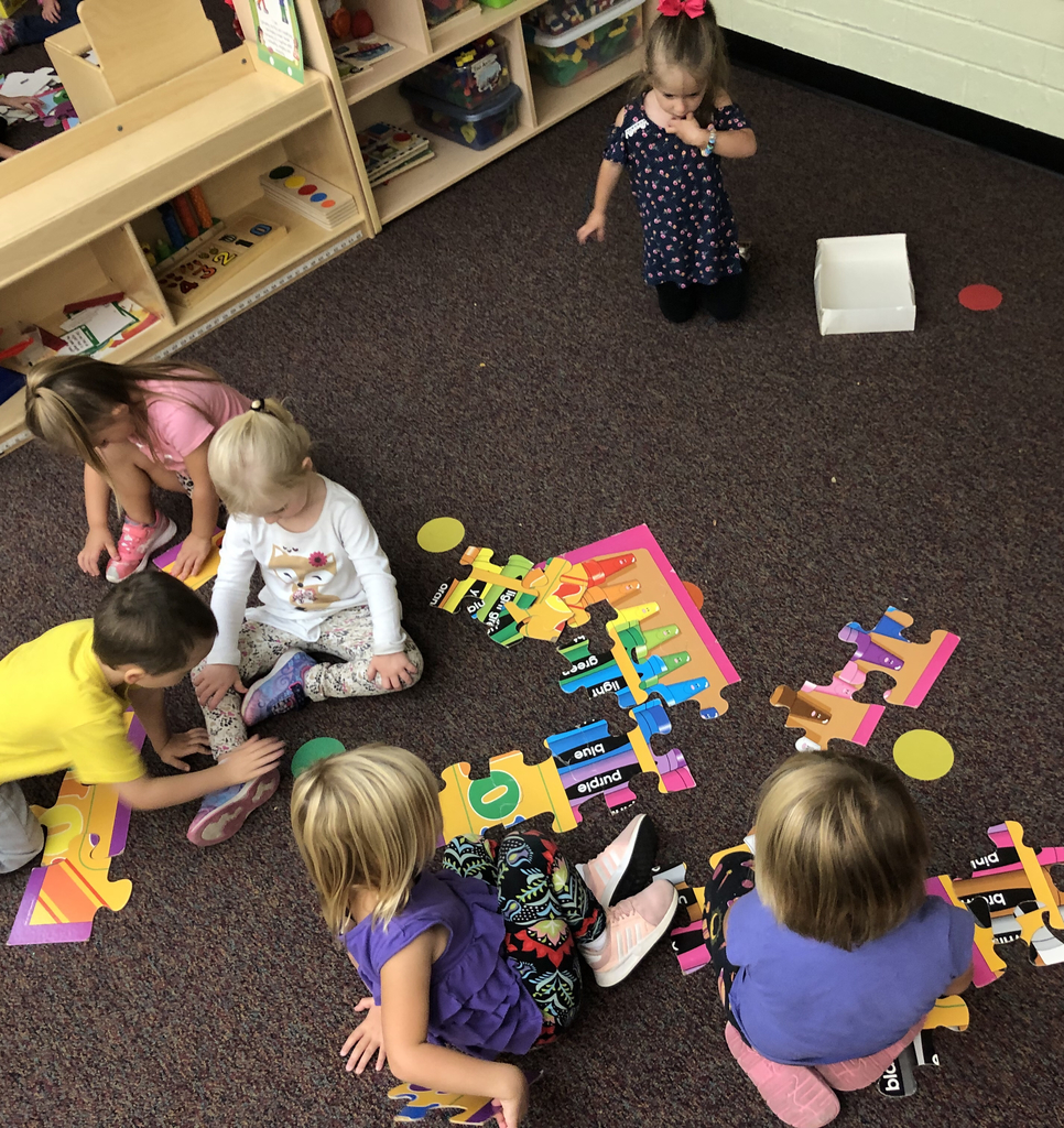 Preschool working together as a team to assemble floor puzzles