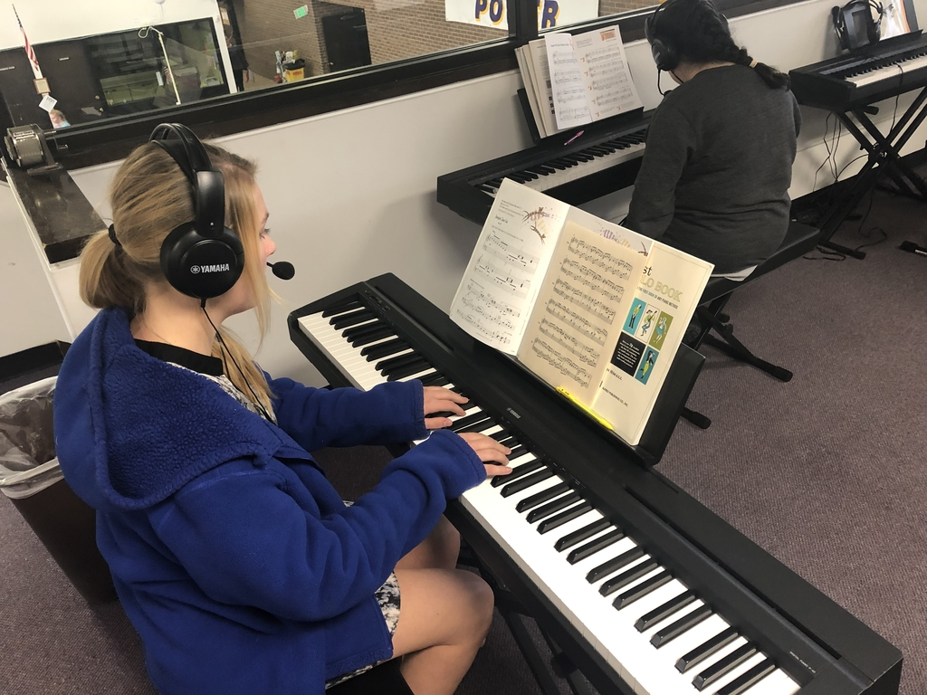 Students working on individual pieces during piano lab.