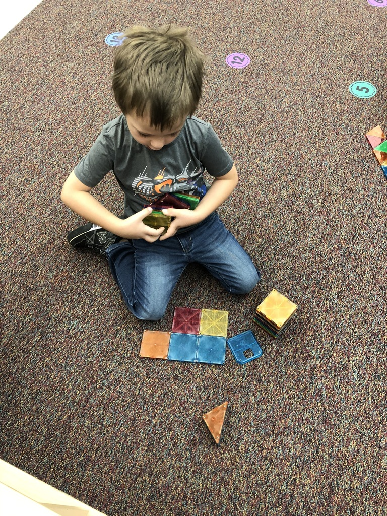 This preschooler is working on building a rocket with magnetic shapes.